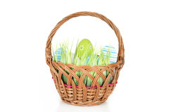 Happy Easter - few eggs on the wooden basket with a grass on the white background Royalty Free Stock Images