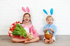 Happy easter! funny funny children   with ears hare getting read. Happy easter! funny funny children boy and girl with ears hare getting ready for holiday Royalty Free Stock Image