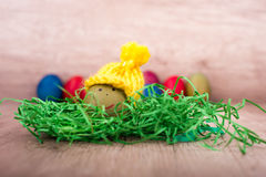 Happy Easter, funny egg with a hat in front of other eggs. Standing on a wooden desk Stock Photography