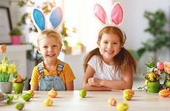 Happy easter! funny funny children with ears hare getting ready for holiday. Happy easter! funny funny children boy and girl with ears hare getting ready for royalty free stock photos