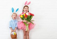 Happy easter! funny funny children   with ears hare getting read. Happy easter! funny funny children boy and girl with ears hare getting ready for holiday Stock Image