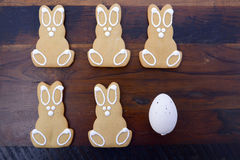 Happy Easter gingerbread cookie bunnies. On a dark wood table background royalty free stock images
