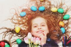 Happy easter girl, colorful eggs in long hair, tulip flowers Stock Photo