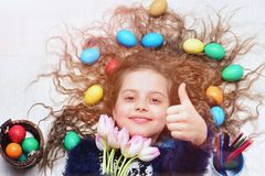 Happy easter girl, colorful eggs in long hair, tulip flowers Royalty Free Stock Image