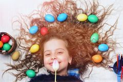 Happy easter girl, colorful eggs in long hair, tulip flowers Stock Image