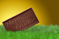 Happy Easter on golden background. Happy Easter text on chocolate bar on golden background Royalty Free Stock Image