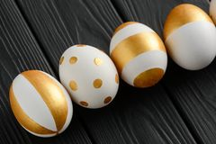 Happy Easter golden decoration set. On black wooden background. Eggs painted with modern patterns, dots and stripes stock image