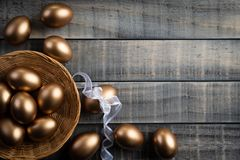 Happy easter! golden of Easter eggs in nest and Feather on wooden background stock image
