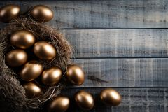 Happy easter! golden of Easter eggs in nest and Feather on wooden background stock photography