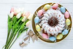 Happy Easter! Golden tray with plate with cake and hand painted colorful eggs, tulips on white wooden table. Close up. Decoration. For Easter, festive royalty free stock photos