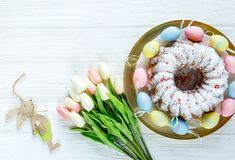 Happy Easter! Golden tray with plate with cake and hand painted colorful eggs, tulips on white wooden table. Close up. Decoration stock photo