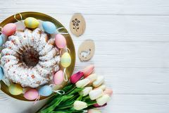 Happy Easter! Golden tray with plate with cake and hand painted colorful eggs, tulips on white wooden table. Close up. Decoration. For Easter, festive stock photo