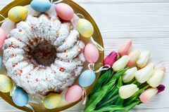Happy Easter! Golden tray with plate with cake and hand painted colorful eggs, tulips on white wooden table. Close up. Decoration. For Easter, festive royalty free stock photography