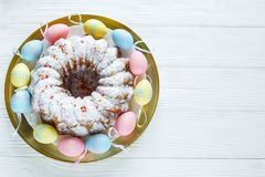 Happy Easter! Golden tray with plate with cake and hand painted colorful eggs, tulips on white wooden table. Close up. Decoration. Happy Easter! Golden tray with stock images