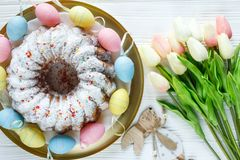 Happy Easter! Golden tray with plate wit cake and hand painted colorful eggs, tulips on white wooden table. Close up. Decoration. For Easter, festive background stock photo