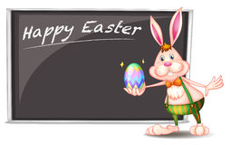 A happy easter greeting with a bunny beside a gray board Stock Photo
