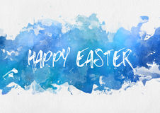 Happy Easter greeting card design. On a band of colorful blue watercolor paint with random splash effect on a textured off-white art paper Royalty Free Stock Photography