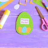 Happy Easter greeting card in egg shape. Easter card made from paper. Materials and tools for children`s creativity Stock Image