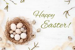 Happy Easter greeting card with Easter eggs in the nest. Spring willow twigs & Vintage lace on white wooden table. Flat lay, top view royalty free stock photography