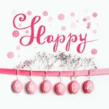 Happy Easter greeting card lettering with hanging pastel pink Easter eggs on ribbon with flowers at white wall background. Happy Easter greeting card text royalty free stock photo