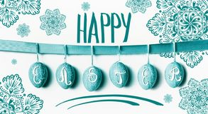 Happy Easter greeting card lettering with hanging turquoise Easter eggs on ribbon with flowers at white wall background royalty free stock photo