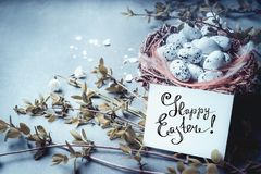 Happy Easter greeting card with lettering, nest with bird eggs and spring twigs and flowers. Stock Photography