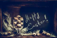 Happy Easter greeting card with Quail eggs  in glass and chalkboard over rustic wooden background Royalty Free Stock Photos