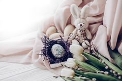 Happy easter greeting card. stylish easter eggs with chick ornam. Ents in nest and bunny rabbit and tulips and willow buds on rustic white wooden background Royalty Free Stock Images