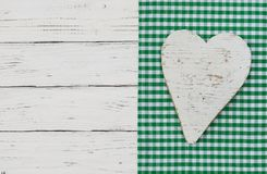 Happy Easter greeting card with white heart on green checked fabric and white wooden table. White wooden heart on green textile border and background with copy stock photos