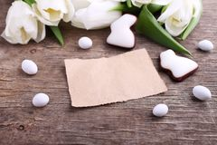 Happy Easter greeting card with white tulip and chocolate eggs and bunny royalty free stock photography