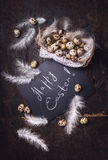 Happy Easter greeting card It is written on chalkboard and decorated quail eggs in basket  and feathers Royalty Free Stock Photography