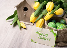 Happy Easter greeting card with yellow tulips and sack of colored Easter Eggs Royalty Free Stock Images