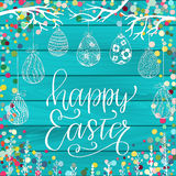 Happy Easter Greeting holiday celebration card. With hand drawn lettering design, hanging eggs, tree twigs and colorful scattered confetti on blue paint wood stock illustration