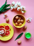 Happy Easter Eggs Red Grapefruits Protein vitamin Pink white apple flowers green aroma candle yellow plate on pink Healthy f. Happy Easter greetings card Holiday royalty free stock photography