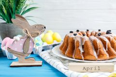 Happy Easter! Handmade cake on towel, eggs, wooden bunny rabbit on blue wooden background. Decoration for Easter stock images