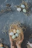 Happy easter. Hands holding easter eggs in nest with easter decoration, top view royalty free stock photography