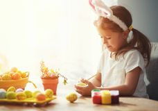 Happy easter! happy child girl paints eggs for holiday stock image