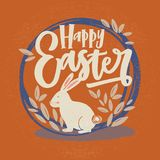 Happy Easter inscription or holiday wish written with cursive font and bunny inside round frame or wreath decorated by. Leaves on orange background. Hand drawn Stock Images