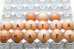 Happy Easter inscription on raw eggs Stock Image