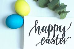 Happy Easter inscription, yellow and blue eggs on a white wooden background. Happy Easter inscription, yellow and blue eggs on white wooden background royalty free stock photos