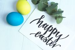 Happy Easter inscription, yellow and blue eggs on a white wooden background. Happy Easter inscription, yellow and blue eggs on white wooden background Stock Photo