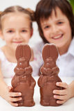 Happy easter kids with large chocolate bunnies Royalty Free Stock Photos