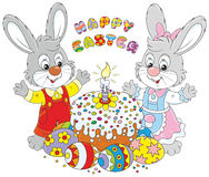 Happy Easter. Happy little rabbits with a decorated Easter cake and colorfully painted eggs Stock Images