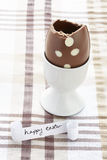 Happy easter message with half eaten chocolate egg Royalty Free Stock Photography