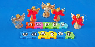 Happy Easter. Message using colorful jigsaw style pieces  with  angels emphasizing the religious element isolated on blue background Royalty Free Stock Photography