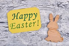 Happy Easter message and wooden rabbit. Yellow Easter greeting card and plywood rabbit on grey textured background. Easter holidays congratulations stock photos