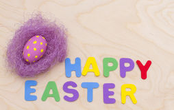 Happy Easter and a nest with an egg. NInscription happy Easter and a nest with an egg Stock Photography