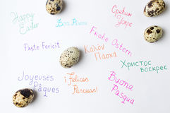 Happy Easter note written in different languages. Happy Easter note in different languages and quail eggs Stock Image