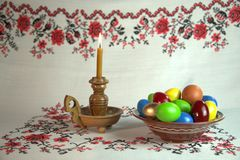 Happy Easter. Orthodox Easter. On a table covered with a tablecloth with ornaments worth plate with colored eggs. Nearby stands a candle in a candlestick. White Royalty Free Stock Image