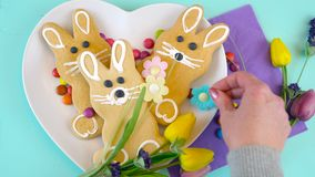 Happy Easter overhead with Easter bunny cookies and candy on a wood table. stock video footage